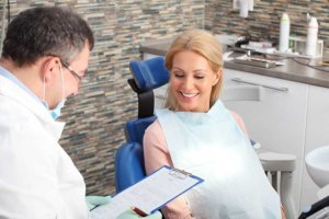 woman in chair talks to best dentist in orlando