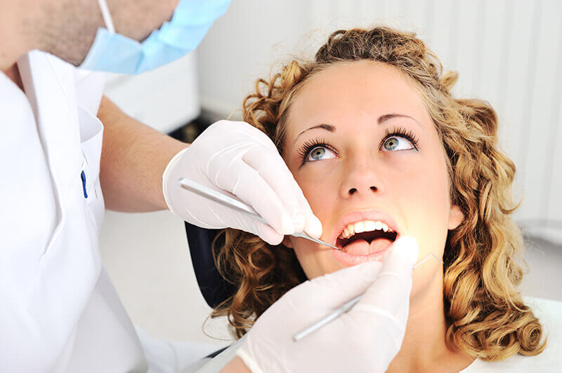 young woman looks at doctor performing cosmetic dentistry