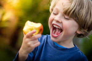 Kid eating an apple which is one of the healthy teeth foods for kids